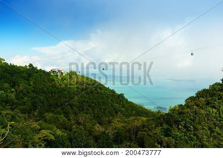 Beautiful tree covered mountains with the andaman sea visble between them, cloudy sky and fog rolling between them. Shot in the Machincang mountain in Langkawi Malaysia