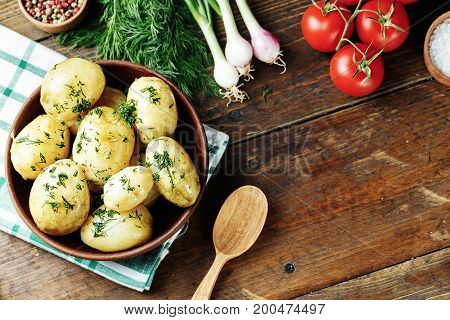 Boiled young potatoes with dill in a clay dish on a napkin top vew space for text