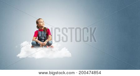 Cute kid girl sitting on cloud against blue color background