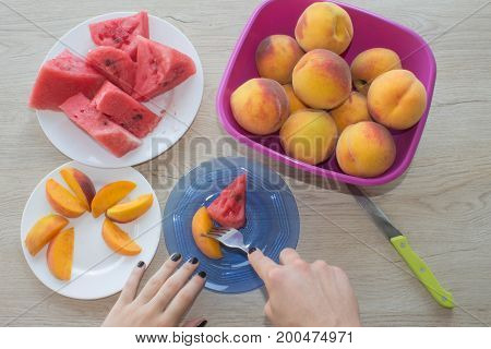 Fresh slices of watermelon and peaches on a plate on the wooden table. Organic Ripe Seedless Watermelon and peaches Cut into Wedges