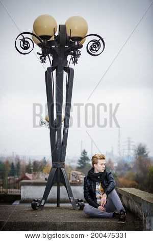 Street fashion. Young fashionable man guy with stylish hair posing outdoor on cityspace background
