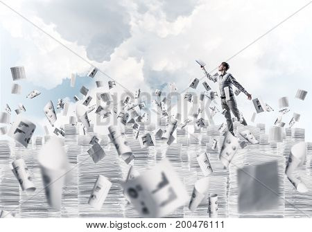 Man in casual wear keeping hand with book up while standing among flying paper documents with cloudly skyscape on background. Mixed media.