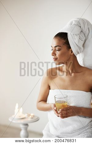 Beautiful african girl with towel on head holding glass smiling looking in side resting in spa resort. Copy space.