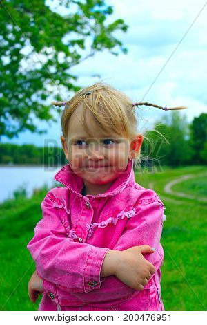 pretty fashionable smiling baby girl with nice plaits near the river