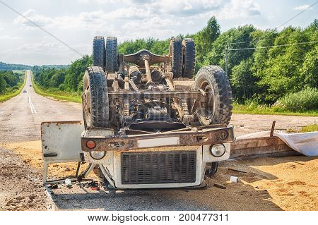 Accident on the road. Overturned truck with sand lies on the ground after a crash