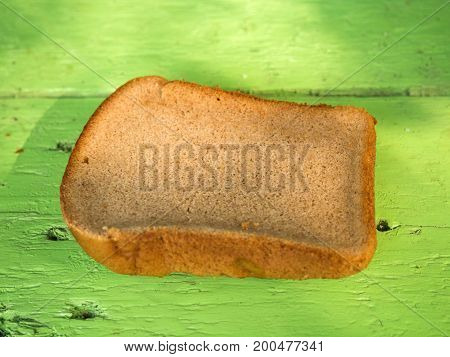 Simple rustic loaf of bread on a wooden table painted green. Rural unpretentious food.
