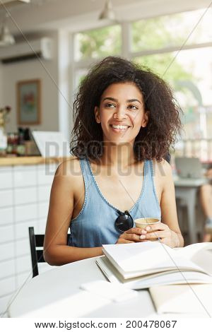 Young beautiful cheerful african girl student smiling laughing sitting in cafe. Books magazines lying on table. Learning and education. Copy space.