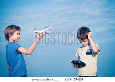 Kids preparing to fly drone in summer day outdoors.