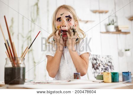 Playful Caucasian female child having fun with spots of paint on her face and opened mouth, touching her face with hands in paint. Little messed up in paint blond girl having fun and playing fool.