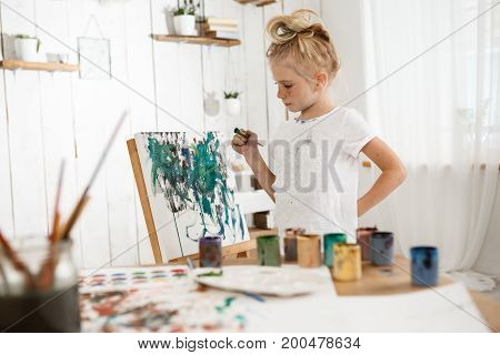 Creative, occupied female child standing behind easel, working on her new picture. Little, cute blonde girl with hair bun in white cloth enjoying art in the art room filled with sunlight.