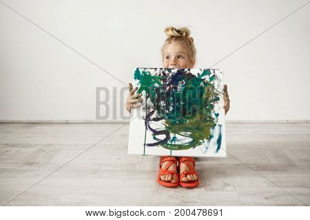Isolated headshot of Caucasian blonde preschool girl showing picture that she painted. Adorable child holding canvas. Happy childhood concept.
