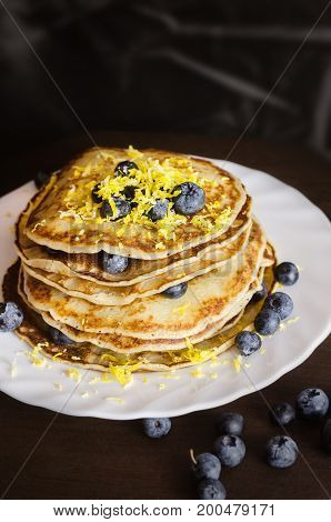 Pancakes with blueberries on white plate on dark background.