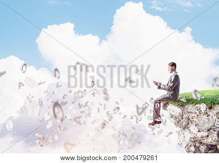 Young businessman sitting on green island with smartphone in hands