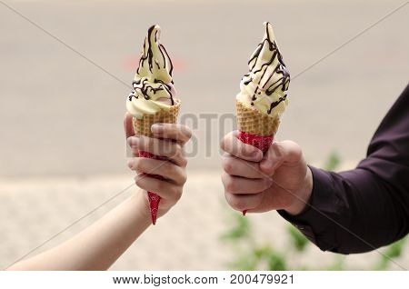 Close-up view of the hands of a boy and a girl holding two ice-cream with chocolate toping in a wafer with a blurred background