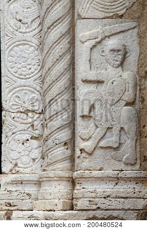 relief with Etruscan warrior characters on ancient church in Sovana ,Tuscany, Italy