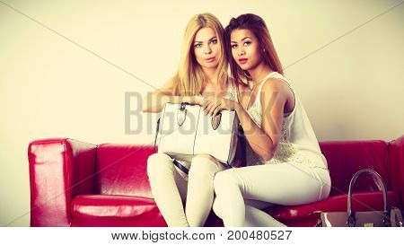 Fashion clothes clothing accessories trendy outfits concept. Two women wearing light outfit and black high heels sitting on red sofa presenting bag