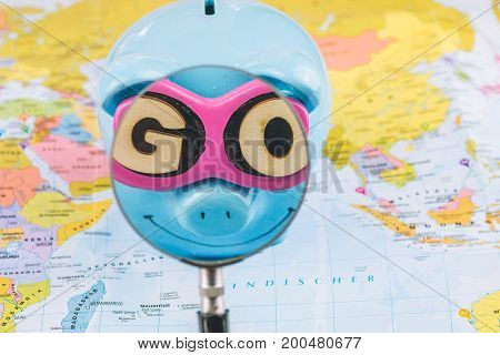 Saving piggy bank with sunglasses. Magnifier zoome into GO slogan. Pig is staying on the world map ready for travel.