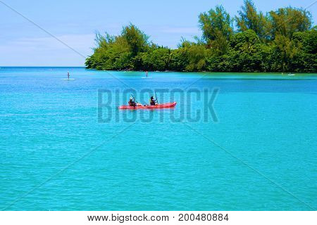 August 1, 2017 at Hanalei Bay in Kauai, HI:  People kayaking on the warm turquoise waters of Hanalei Bay where people can swim, kayak, sunbathe, and relax at the bay surrounded by a beautiful landscape taken in Kauai, HI