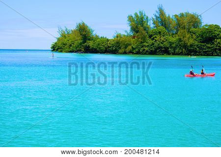 August 1, 2017 at Hanalei Bay in Kauai, HI:  People kayaking at Hanalei Bay on turquoise blue water surrounded by a tropical forest and the Pacific Ocean taken at Hanalei Bay where people can swim, kayak, paddle board, and relax on the water at the beach