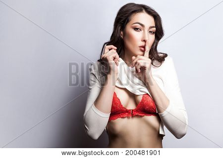 Secret between us do not tell anyone. Sexy young fashion model undressing and looking at camera