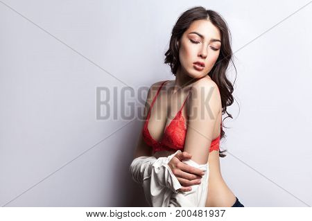 Young sexy body. Beautiful erotic young model on red bra with vawy hair undressing and closed eyes. Isolated on gray background studio shot