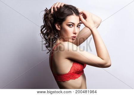 Young sensuality model colects hair and looking at camera. Isolated on gray background studio shot