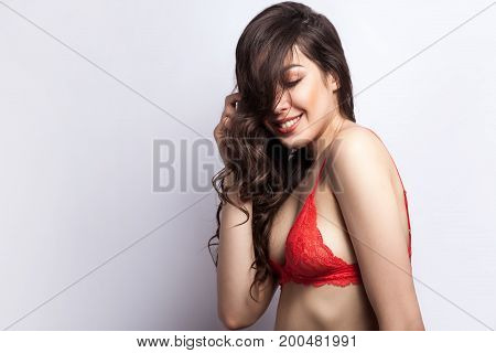 Happiness sensuality model toothy smile and closed eyes. Studio shot on gray background