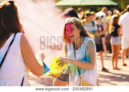Girl spends paint holi, fun smile on her face bright colors