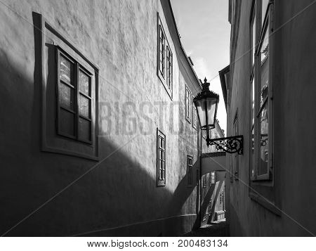Morning Prague scene. Sunlit and long shadows on the wall with gas street lamp, Thunovska Street, Lesser Town, Prague, Czech Republic. Black and white image