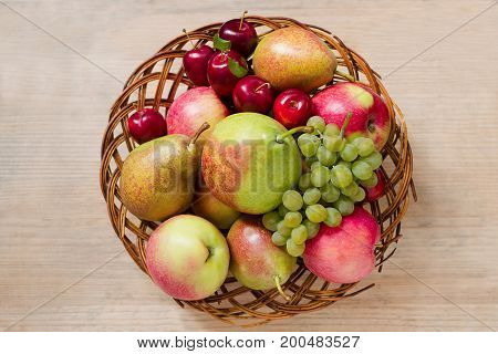 Fresh Ripe Fruit - Apples, Pears, Grapes And Plums In A Wicker Wooden Plate On A Wooden Table. View