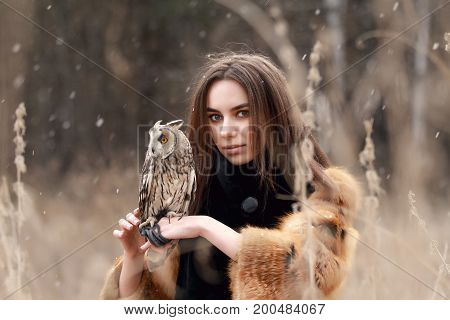 Woman in fur coat with owl on hand by first autumn snow. Beautiful brunette with long hair in nature holding an owl. Romantic delicate look girls