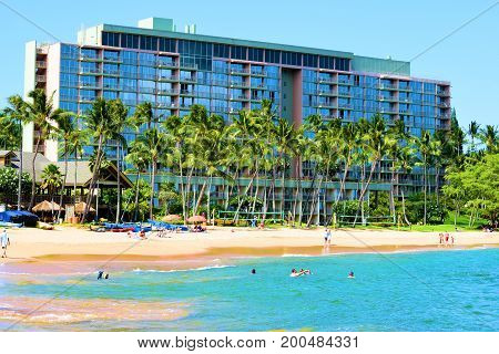 August 1, 2017 at Lihue in Kauai, HI:  Marriott Hotel Resort Kalapaki Bay surrounded by Palm Trees and a sandy beach where guests can sunbathe on the sandy beach or swim and surf in the ocean taken at Lihue in Kauai, HI