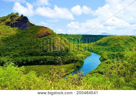River surrounded by a lush green tropical forest taken in the Island of Kauai, HI