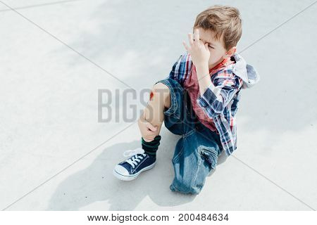 Injured little boy sitting on concrete floor with a scraped knee