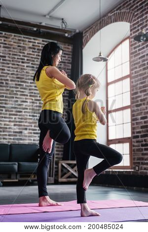 Mother and daughter wearing sports clothing practicing yoga together meditating standing on one leg with hands in prayer position in loft apartment.
