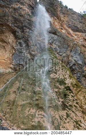 Rinka waterfall in beautiful Alpine valley, Logarska dolina - Logar valley in Slovenia. It's a popular tourist hiking destination in pristine nature surrounded by mountains