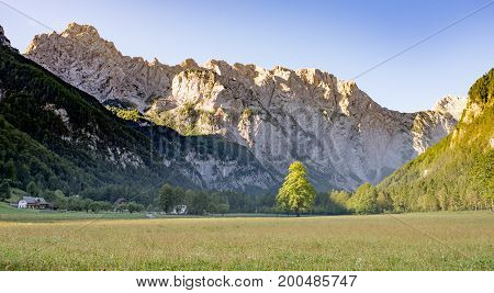 Logarska dolina - Logar valley, Slovenia in sunrise, mountain peaks brightly lit by golden colors of the sun. A popular tourist and travel destination with many Landmarks and offers great hiking and climbing tours