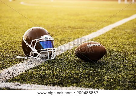 American Football Helmet and ball on green grass pattern for football sport, Football field, soccer field, team sport texture. White stripe on it. Close up focus. Flare sunlight for text and design