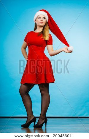 Xmas seasonal clothing winter christmas concept. Young slim woman wearing Santa Claus helper costume red dress. Studio shot on blue background.