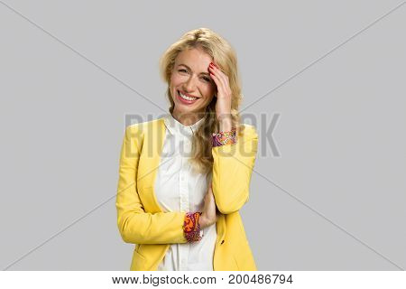 Portrait of cheerful young business woman. Happy smiling young lady close up over grey background.