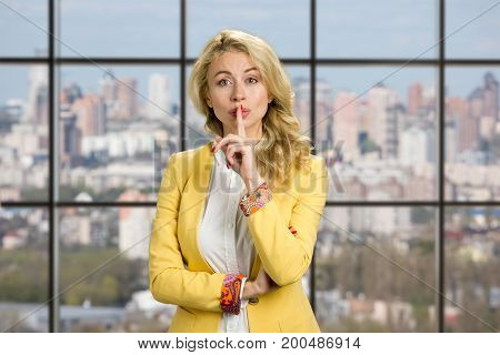 Young business woman gesturing silence. Beautiful young office manager making silence gesture on business center window background.
