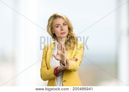 Young business woman gesturing stop. Young blond business lady shows stop gesture.
