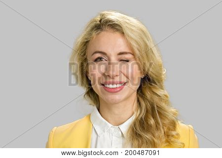 Portrait of smiling twinkling woman. Close up playful young woman closed one eyeisolated on grey background.