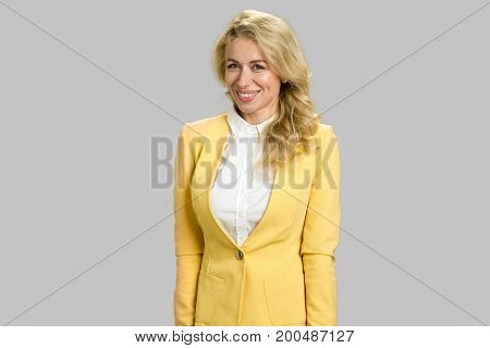 Intelligent beautiful smiling woman. Bright picture of young slim woman in yellow jacket standing on grey background.