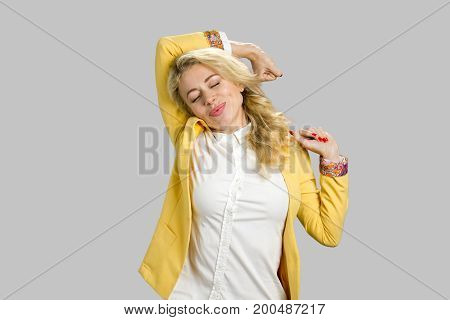 Drowsy business woman stretching, grey background. Attractive tired fatigued young manager stretching extending arms, back, shoulders with closed eyes isolated on grey background.