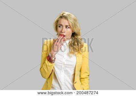 Young yawning woman looking away. Closeup portrait young blond woman placing hand covering mouth, yawning, looking away bored on isolated on grey background.