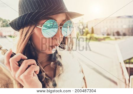 Pretty young girl vape popular ecig gadget, vaping device.Happy brunette vaper girl with e-cig.Portrait of smoker female model with electronic cigarette vaporizer.Ejuice vaping with fruit flavor liquid