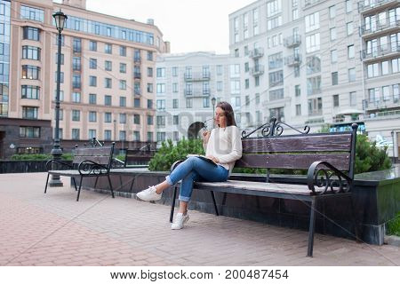 A Beautiful Young Girl With Long Brown Hair Sitting On The Bench With Book And Biting Glasses While