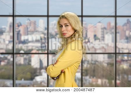 Portrait of young beautiful office worker. Young female manager standing with crossed arms on office window background, side profile.