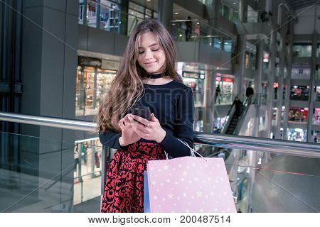 young shopper lady with cellphone and colorful bags